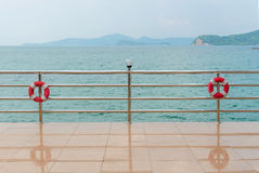 red Lifebuoy on railing by the sea Royalty Free Stock Photos
