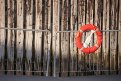 Red lifebuoy with rope on metal railings Stock Photos