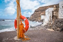 Red lifebuoy with rope on pole with coast and ocean in background. Typical red lifebuoy with rope on pole with coast and ocean in background Royalty Free Stock Image
