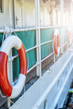 Red lifebuoy with rope on weathered boat. Wall in port Stock Photo