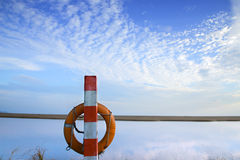 Red lifebuoy. On sandy beach in cloudy day Stock Photography