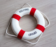 Red lifebuoy with welcome aboard text. Over wooden background stock image