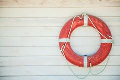 Red lifebuoy on a white wooden wall. Background, copyspace stock image
