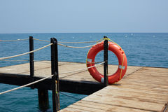 Red Lifebuoy on wooden pier Stock Images