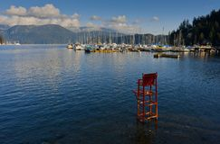 Red Lifeguard Chair. A red lifeguard chair stands in the water at Deep Cove, North Vancouver, Canada royalty free stock image