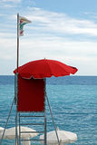 Red  lifeguard tower with white flag over clear blue sky Stock Photo
