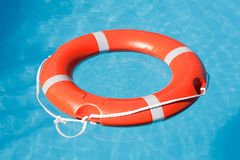 Red lifesaving float. On blue water Stock Photo