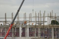Red lift cranes with workers under construction. stock image
