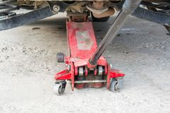 Red lift jack is under the car. Professional pneumatic jack with long grip royalty free stock images