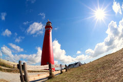 Red lighhouse tower and sun star Stock Photography