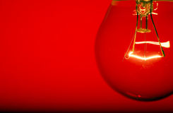 Red Light. Close up of light bulb against blue background - shallow depth of field Stock Image