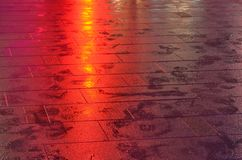 Wet sidewalk lit by red light beam royalty free stock photography