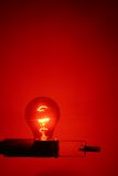 Red Light District. A Red lightbulb casts a red glow Royalty Free Stock Photos