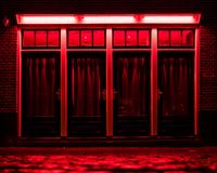 Red Light District in Amsterdam. Red boxes with curtains and wet Cobbles on the street. Red Light District in Amsterdam. Red boxes with curtains and wet rainy stock photo