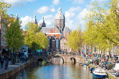 Red light district, crowd of tourists go sightseeing, the Church of St. Nicholas is visible in the distance. royalty free stock images