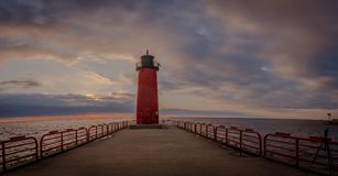 Red light house on Lake Michigan in Milwaukee Wisconsin at sunrise. Sunrise on Lake Michigan with a red light house Stock Photo
