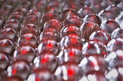 Red Light Reflects off Clear Marbles. Red light reflects off of rows of clear marbles often used to play games royalty free stock photography