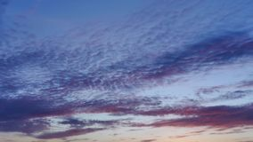Dramatic sky with red light of rising sun suffuses dark blue clouds at morning. Time lapse stock video footage