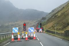 Red light at road works and traffic cones with safety sign at rural isolated mountain scene. Uk stock photography