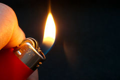 Red lighter. A close up of a red lighter hold by a hand Royalty Free Stock Images