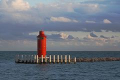 Red lighthouse. Small red lighthouse in the ocean with overcast sky Royalty Free Stock Images