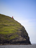 Red lighthouse. On cliff looking over the ocean. Faeroe Islands royalty free stock photography