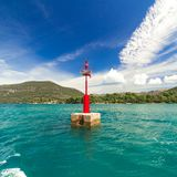 Red lighthouse on the background of the blue Mediterranean Sea in Croatia, sunny day Stock Photos