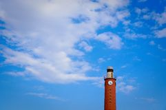 Red lighthouse and blue sky. Tall lighthouse tower with clock on top in daytime. blue sky, white cloud Stock Photos