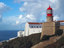 Red lighthouse on Cabo de Sao Vicente with stone wall stock image