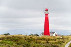 Two lighthouses in the dunes. Red lighthouse in the dunes of the Dutch island Schiermonnikoog, next to it the white house of the lighthouse keeper, in the royalty free stock images