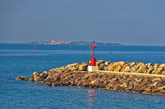 Red lighthouse at entrance to small ferry harbor in Sardinia Stock Images