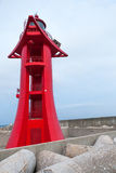 Red lighthouse in harbor with sky on background Royalty Free Stock Photography