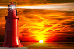 Red Lighthouse with Light Beam at Sunset Royalty Free Stock Photography