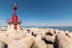 Red lighthouse that marks the entrance of the port. Stock Image