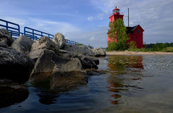 Red lighthouse near Lake Michigan with breakwater Stock Photography