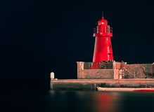 Red Lighthouse by Night. Romantic frontal view of a red lighthouse by night Stock Photo