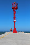 Red lighthouse on the pier with a man sitting Stock Photo