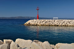 Red lighthouse in port with stones and white bench Stock Photography