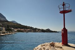 Red lighthouse in port. Podgora, Croatia Stock Image