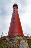 Red lighthouse on a stone hill. With rails and flowers Stock Images