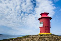 Red lighthouse in Stykkisholmur, Snaefellsnes peninsula, Iceland. Red lighthouse and a cloudy sky in Stykkisholmur, Snaefellsnes peninsula, Iceland Royalty Free Stock Image