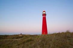 Red lighthouse at sunset on island coast Royalty Free Stock Photos
