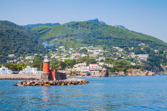 Red lighthouse tower on stone breakwater. Ischia Stock Photography