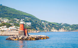 Red lighthouse tower on stone breakwater, Italy Royalty Free Stock Photos