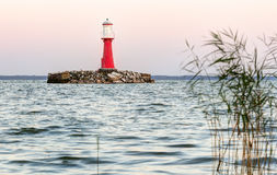 Red lighthouse in the water during sunset. Pervalka village, Lithuania Stock Photography
