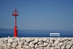 Red lighthouse and white bench on stones Royalty Free Stock Images