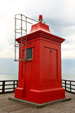 Red lighthouse on wooden jetty Stock Photography