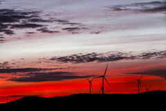 Red lights of dawn with windmills at horizon Royalty Free Stock Image