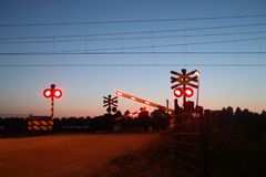 Red lights and signs on a railroad crossing in Moordrecht while sunset is coloring the sky blue and orange.. Red lights and signs on a railroad crossing in royalty free stock image