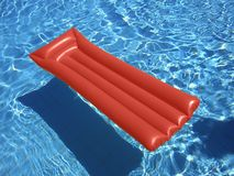 Red Lilo. Floating on a swimming pool Royalty Free Stock Photo
